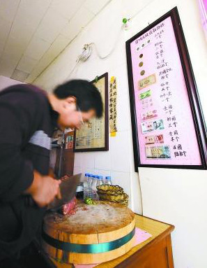 Preparing donkey burgers with price list in ancient Chinese coins hanging on wall