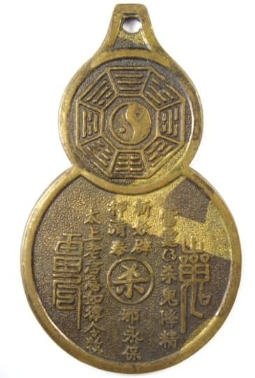 Reverse side of           old Chinese gourd charm displaying Daoist (Taoist) magic           writing, bagua and taiji