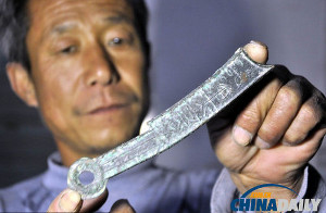 A farmer from Shandong displays the knife money he discovered from the ancient State of Qi