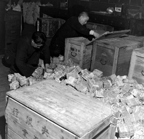Local bank employees removing paper money from wooden boxes