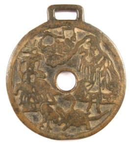 Obverse side             of old charm with traditional symbols